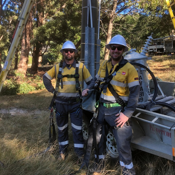 {cf_related_case_studies2 Powercor employees in their uniforms, wearing harnesses and hardhats in preparation for climbing a power pole.